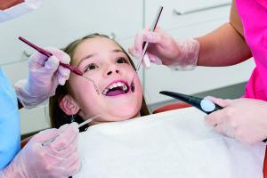 Mädchen liegt entspannt mit offenem Mund bei Zahnuntersuchung