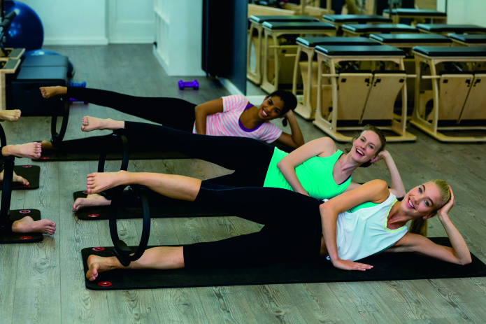 Smiling fit women exercising with pilates ring