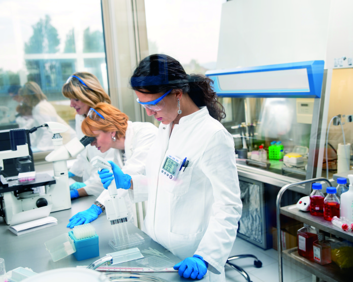 Photo of three real female scientists researching in laboratory.